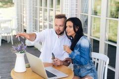 Atrakcyjni młodzi kochankowie siedzą przy stołem w kawiarni, dyskutują coś, mężczyzna punkty coś Faceci używają laptop obraz royalty free