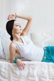 Atrakcyjni potomstwa garbnikująca kobieta w orientalnej biżuterii kłama na białym łóżku Obrazy Royalty Free