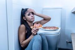 Atrakcyjni potomstwa i smutnego bulimic młodej kobiety uczucia łasowanie winny i chory podczas gdy siedzący na podłodze obok toal zdjęcie royalty free