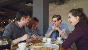 Atrakcyjni ucznie opowiadają śmiać się robić wysokości i gestykulujący podczas gdy łomotający jedzący pizzę w kawiarni szczęśliwi zbiory