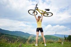 Atrakcyjny żeński cyklista z żółtym halnym bicyklem, cieszy się słonecznego dzień w górach zdjęcie royalty free