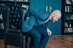 Atrakcyjny łysy brodaty mężczyzny mienie na jego z powrotem, próbujący wstawać od jego rzemiennego krzesła Bogaci ludzie płaczą z zdjęcia stock