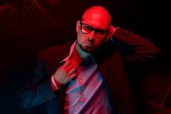 Atrakcyjny łysy mężczyzna z brodą z szkłami na neonowego światła tle obrazy stock