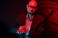 Atrakcyjny łysy mężczyzna z brodą z szkłami na neonowego światła tle obrazy royalty free