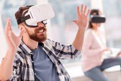 Atrakcyjny śmieszny mężczyzna próbuje uchwytać VR przedmioty Fotografia Stock