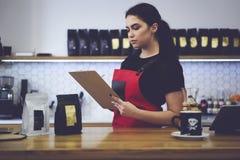 Atrakcyjny żeński administracyjny kierownik robi przeglądowi sprawdza kwotę produkty liczy miesięcznego dochód Obrazy Royalty Free