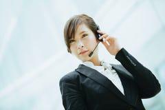 Atrakcyjny żeński Azjatycki bizneswomanu być ubranym hełmofony z mikrofonem Fotografia Royalty Free