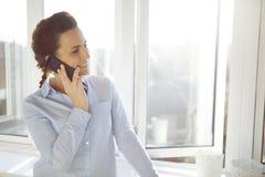 Atrakcyjny żeński kierownictwo opowiada na jej telefonie komórkowym zdjęcia royalty free
