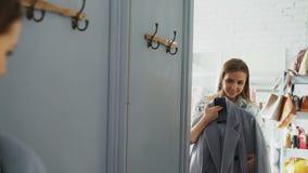 Atrakcyjny żeński klient wybiera żakiet w trafnym pokoju i sprawdza tkaninę, przyglądający na wolności lustro Jest zdjęcie wideo