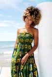 Atrakcyjny afrykanina model opiera przeciw ścianie w sukni przy plażą Zdjęcie Royalty Free