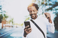 Atrakcyjny amerykański afrykański murzyn słucha muzyka z hełmofonami w miastowym tle Szczęśliwi mężczyzna używa smartphone fotografia royalty free