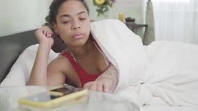 Atrakcyjny amerykanin afrykańskiego pochodzenia kobiety dosypianie pod białą koc w lekkim pokoju na tle Alarm na zdjęcie wideo
