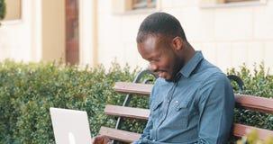 Atrakcyjny amerykanina afrykańskiego pochodzenia mężczyzna pracuje na laptopie siedzi na ławce Otrzymywający dobre wieści excited zbiory
