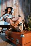 Atrakcyjny artystyczny kobiety obsiadanie na ławce z nogami na walizce w drewnianym obrazy stock