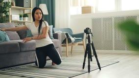 Atrakcyjny Azjatycki blogger wtedy siedzi na podłodze i nagraniu instaluje kamerę na tripod i przystosowywa wyposażenie zdjęcie wideo