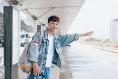 Atrakcyjny azjatykci mężczyzna powstrzymywania taxi przy lotniskiem obraz royalty free