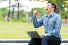 Atrakcyjny azjatykci szczęśliwy mężczyzna gest lub podwyżki ręka excited krzyczącego tak czyta online dobre'u wieści lub socjalny zdjęcia stock