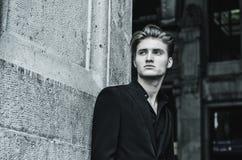 Atrakcyjny błękit ono przyglądał się, blond młody człowiek opiera przeciw biel ścianie Obraz Royalty Free