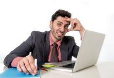 Atrakcyjny biznesmen przy biurowym biurkiem pracuje na komputerowego laptopu przyglądający zmęczonym, ruchliwie i Obrazy Stock