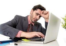 Atrakcyjny biznesmen w kostiumu i krawacie pracuje w stresie przy offi Obrazy Royalty Free