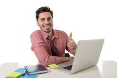 Atrakcyjny biznesmen w koszula i krawata obsiadaniu przy biurowym biurkiem pracuje z komputerowym laptopem daje kciukowi up Obrazy Royalty Free