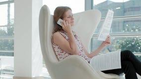 Atrakcyjny biznesmena obsiadanie na białym krześle w szklanym biurze i sprawdza dokumenty zbiory