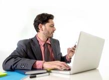 Atrakcyjny biznesmena obsiadanie przy biurowym biurkiem pracuje w stresie na komputerowym laptopie opowiada na telefonie komórkow Obraz Royalty Free