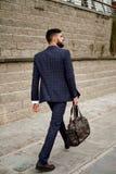 Atrakcyjny biznesmena odprowadzenia puszek uliczna mienie podróży torba zdjęcie stock