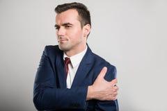 Atrakcyjny biznesowego mężczyzna mienia ramię jak kaleczenie zdjęcia stock