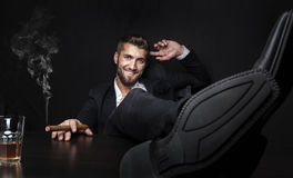 Atrakcyjny biznesowy mężczyzna z cygarem i napojem zdjęcia royalty free