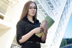 Atrakcyjny bizneswoman jest ubranym szkła trzyma falcówkę Fotografia Royalty Free