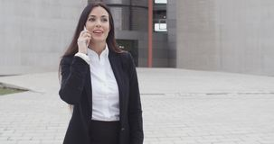 Atrakcyjny bizneswoman sprawdza jej telefon komórkowego zdjęcie wideo
