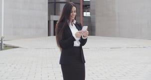 Atrakcyjny bizneswoman sprawdza jej telefon komórkowego zbiory