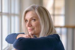 Atrakcyjny blond kobiety dopatrywanie przez okno zdjęcia stock