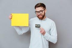 Atrakcyjny brodaty biznesmena mienia copyspace puste miejsce i karta debetowa Zdjęcia Stock