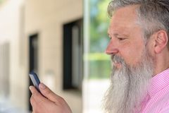 Atrakcyjny brodaty mężczyzna czyta wiadomość tekstową obraz stock