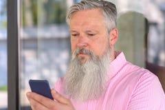 Atrakcyjny brodaty mężczyzna czyta wiadomość tekstową fotografia stock