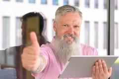 Atrakcyjny brodaty mężczyzna trzyma pastylka komputer osobistego obraz stock