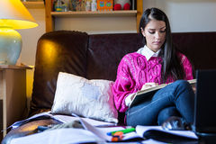 Atrakcyjny brunetki kobiety ucznia reading/studiowanie w jej girly pokoju Zdjęcia Stock