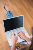 Atrakcyjny brunetki obsiadanie na podłoga używać jej laptop Obraz Stock