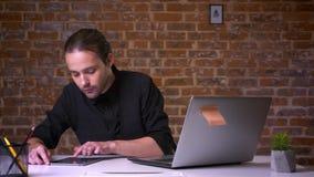 Atrakcyjny caucasian dorosły mężczyzna swiping jego pastylkę i patrzeje komputer podczas gdy siedzący w ceglanym biurze w czarnym