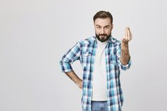 Atrakcyjny caucasian facet patrzeje szalenie i gniewny, trzymający rękę na talii podczas gdy pokazywać dostaje punktu gest z fotografia royalty free