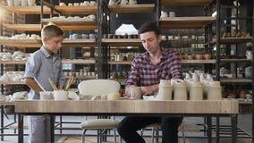 Atrakcyjny caucasian mężczyzna robi ceramicznym garnkom podczas gdy jego syn przychodzi garncarstwo zbiory wideo