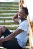 Atrakcyjny czarny męski obsiadanie outdoors i ono uśmiecha się Zdjęcie Royalty Free