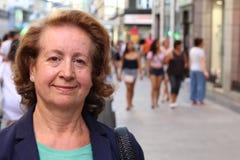 Atrakcyjny dorośleć starzejącej się kobiety przeciw ruchliwie miasto ulicie z udziałami ludzie i kopiuje przestrzeń Obrazy Stock