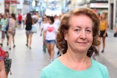 Atrakcyjny dorośleć starzejącej się kobiety przeciw ruchliwie miasto ulicie z udziałami ludzie i kopiuje przestrzeń Zdjęcie Royalty Free