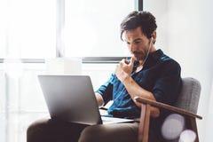 Atrakcyjny dorosły biznesmen pracuje przy biurem Obsługuje używać współczesnego notatnika na hełmofonach w roczniku podczas gdy s Fotografia Royalty Free