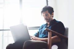 Atrakcyjny dorosły mężczyzna pracuje w domu Obsługuje używać współczesnego laptop i hełmofony w rocznika krześle podczas gdy sied Obrazy Royalty Free