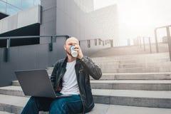 Atrakcyjny dorosły pomyślny łysy brodaty mężczyzna w czarnej kurtce używać laptop i pijący kawę w schodkach przy miastem zdjęcie stock