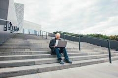 Atrakcyjny dorosły pomyślny łysy brodaty mężczyzna w czarnej kurtce używać laptop w schodkach przy miastem obrazy royalty free